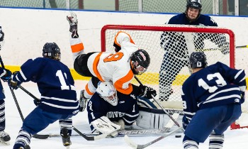 Thayer junior C Jay O'Brien crashes into Andover PG goalie Kyle Martin.
