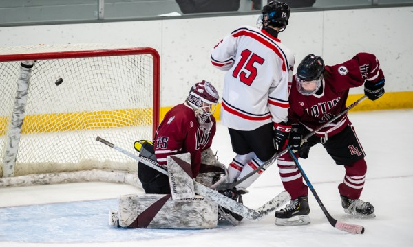 St. George's freshman Julian Frias (#15) deflects the puck past Roxbury Latin senior goaltender Mikey Jones in the first period of the Dragons' 3-1 ro